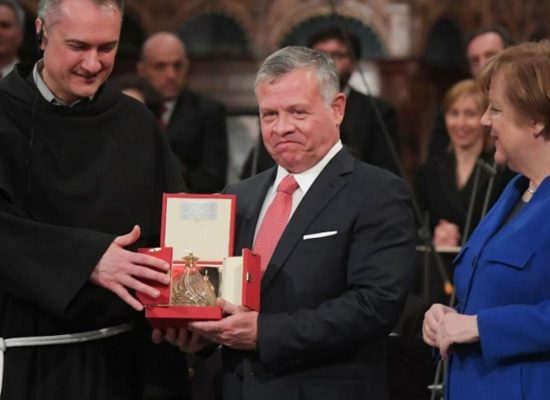 "King Abdullah II of Jordan (C) receives from Guardian of the Sacred Convent of Assisi, Father Mauro Gambetti (L) the Lamp of the Peace of St. Francis, the ""Catholic Nobel"", as German Chancellor Angela Merkel (R) looks on during a ceremony at the Basilica of St. Francis of Assisi, on March 29, 2019 in Assisi. (Photo by Tiziana FABI / AFP)"