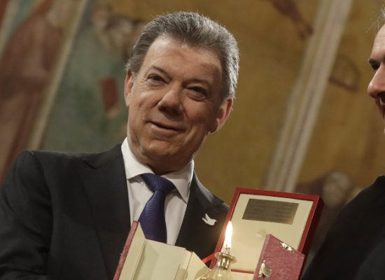 Colombian President Juan Manuel Santos receives the St. Francis lamp peace prize  by  Father Mauro Gambetti during a ceremony in Assisi's Basilica, Italy, Saturday Dec. 17, 2016. Pope Francis is doing his part to unite Colombians divided by a peace deal with leftist rebels by sponsoring a surprise meeting on Friday between President Juan Manuel Santos and his harshest critic. (AP Photo/Gregorio Borgia) |