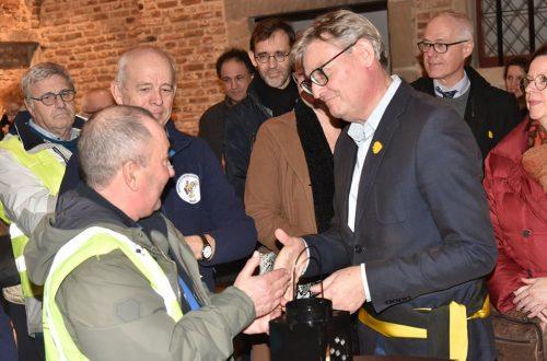 Schepen de Coene ontvangt het vredeslicht in Kortrijk.